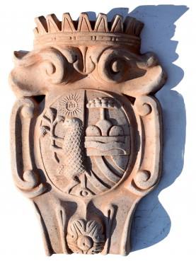 Stemma in terracotta bipartito con IHS e Agnello contrapposto all'albero dei Della Gherardesca