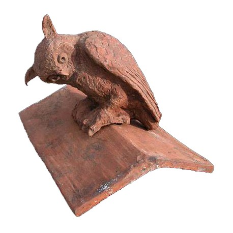 Owl on the top of an ancient saddle roof tile