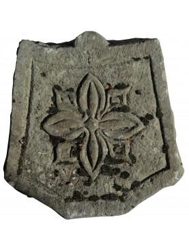 Stemma in pietra con fiore a otto petali
