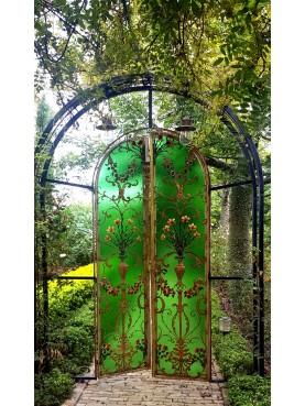 Porta liberty in vetro e ferro battuto inserita in un giardino