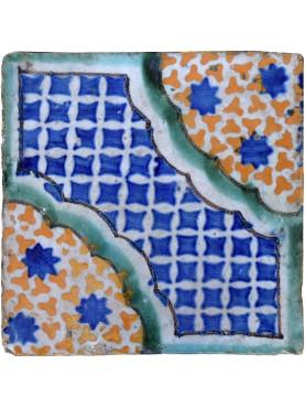 Antica piastrella di maiolica con stelle azzurre