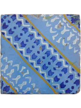 Ancient majolica tile blue, white and yellow on a light blue background