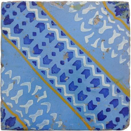 Antica piastrella di maiolica blu, bianca e gialla su sfondo celeste